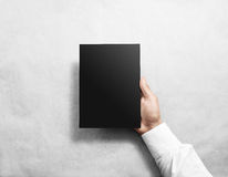 Hand holding blank black brochure booklet mockup. Royalty Free Stock Photo