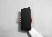 Hand holding blank black opened brochure booklet. Royalty Free Stock Images