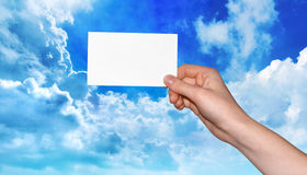 Hand holding blank business card. Woman's hand holding a blank business card in front of a blue sky stock photo