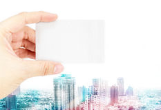 Hand holding blank business card with overly color with cityscap Stock Photo