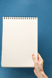 Hand holding blank notepad Stock Photography