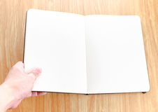 Hand holding blank open notebook lay it on wooden table,Template Stock Photography