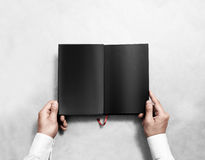 Hand holding blank opened book mock up with black pages. Stock Image