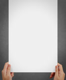 Hand holding a blank paper sheet with both hands Stock Images