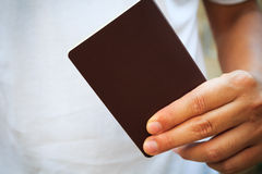 Hand holding blank passport. Hand holding brown blank passport Royalty Free Stock Photo