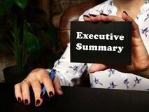 Hand holding a blank piece of paper with inscription Executive Summary . Close up white business card