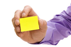 Hand holding blank post-it note. Hand holding blank yellow post-it note ready for message stock photography