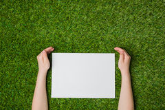 Hand holding blank sheet of paper over grass Stock Photo