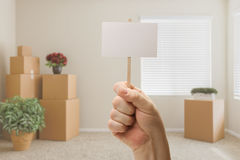Hand Holding Blank Sign in Empty Room with Packed Moving Boxes Stock Photography