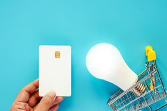 Hand holding a blank white credit card with glowing LED light bu stock photography