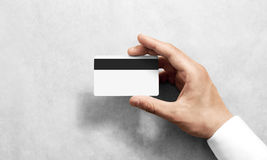 Hand holding blank white credit card mockup black magnetic stripe. Hand holding blank white credit card mockup with black magnetic stripe, back side view Stock Image