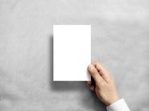 Hand holding blank white vertical postcard flyer mockup.