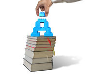 Hand holding block completing letter A blocks on stack books Royalty Free Stock Photography