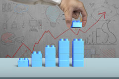 Hand holding blue block complete growth bar graph shape Stock Images