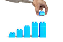 Hand holding blue block complete growth bar graph shape Royalty Free Stock Image