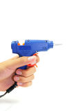 Hand holding blue glue gun. On white background Stock Photos