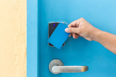 Hand holding blue hotel keycard in front of electric door Royalty Free Stock Photography