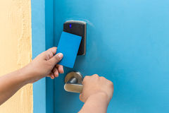 Hand holding blue hotel keycard in front of electric door Royalty Free Stock Images