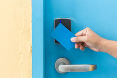 Hand holding blue hotel keycard in front of electric door Royalty Free Stock Image