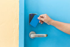 Hand holding blue hotel keycard in front of electric door Stock Photos