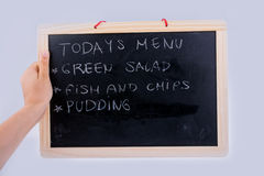 Hand holding the board  with the menu of the day Stock Image