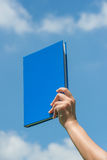 Hand holding book over blue sky Stock Photography