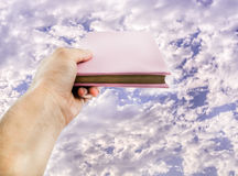 Hand holding a book towards sky. Royalty Free Stock Photography