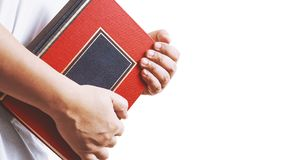 Hand holding the book on white. Background Royalty Free Stock Photography