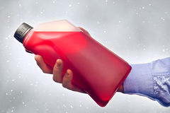 Hand Holding a Bottle of Antifreeze Stock Images