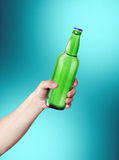 Hand holding a bottle. Template for the ability to use any brand label on a blue background Royalty Free Stock Photo