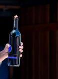 Hand holding bottle of wine Stock Photo