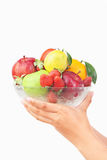 Hand holding bowl of fruits Stock Photo