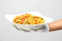 Hand holding a bowl of pasta. A person holding a bowl of pasta with pepper sauce Stock Photo