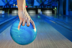 Hand holding a bowling ball. The hand holding the bowling ball in the background of the playing field Royalty Free Stock Photo