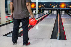 The hand holding the bowling ball in the background of the playing field. Man holding a bowling ball on the background of the playing field Royalty Free Stock Photos