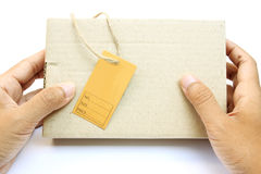 Hand holding a box with brown empty paper tag Royalty Free Stock Images
