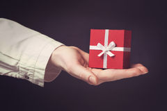 Hand holding box for a gift isolated on black. Hand holding box for a gift isolated on a black background Royalty Free Stock Image