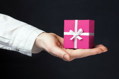 Hand holding box for a gift isolated on black. Background Stock Images