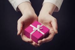 Hand holding box for a gift isolated on black. Hand holding pink box for a gift isolated on a black background Royalty Free Stock Photography