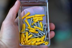 Hand holding box of screws and plastic anchors royalty free stock photography