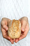 Hand holding bread. Close up of female hands holding whole grain roll Royalty Free Stock Images