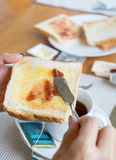 Hand holding bread with fruit jam and tea cup Royalty Free Stock Photography