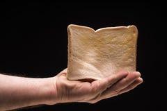 Hand holding bread toast isolated on black background, studio shot Stock Image