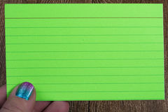 Hand holding a bright green index card Stock Image