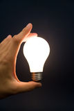 Hand holding a Bright Light Bulb Royalty Free Stock Photography