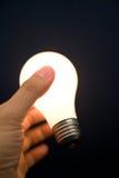 Hand holding a Bright Light Bulb Stock Photo