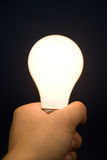 Hand holding a Bright Light Bulb Stock Photo