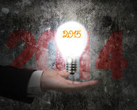 Hand holding brightly 2015 light bulb illuminated old concrete w Stock Image