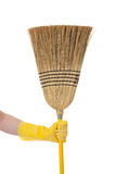 Hand holding Broom - Chore or housework theme. A yellow gloved hand holding a corn broom on a white background royalty free stock photos