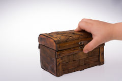 Hand holding a brown wooden case. On a white background Royalty Free Stock Image